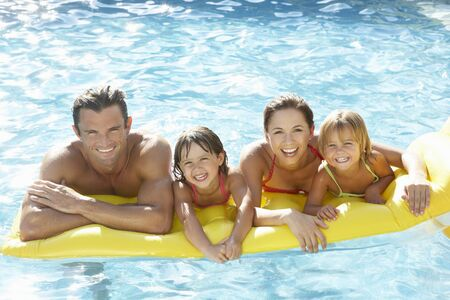 women having fun: Young family, parents with children, in pool Stock Photo