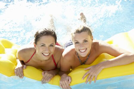 Two women friends having fun together in pool photo