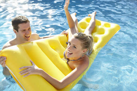 Young couple having fun in pool photo