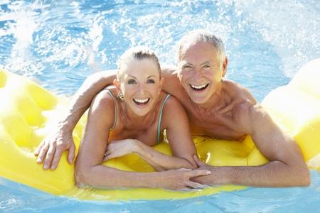 anciano feliz: Pareja Senior que se divierten en la piscina