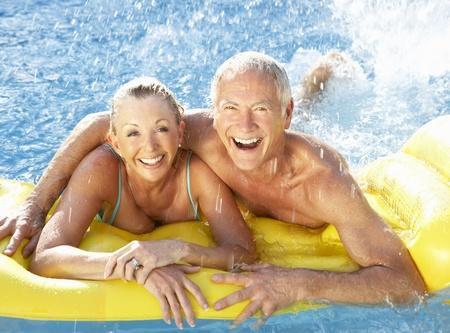 matress: Senior couple having fun in pool