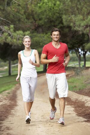 Young couple running through park photo