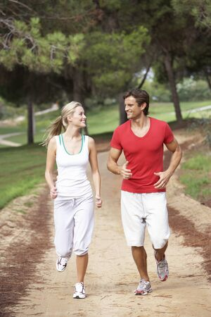 Young couple running in park photo