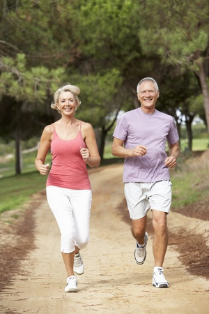 Senior couple running in park photo