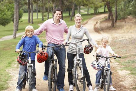 ni�os en bicicleta: Familia disfrutando de paseo en bicicleta en el Parque Foto de archivo
