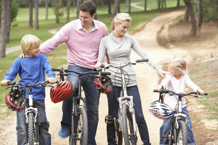 Family enjoying bike ride in park photo