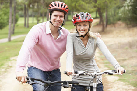 Couple riding bicycle in park Stock Photo - 8514464