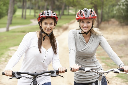 Two Female friends riding bikes in park Stock Photo - 8505191