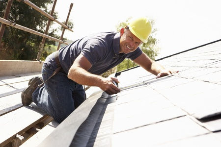 Roofer Working On Exterior Of New Home photo