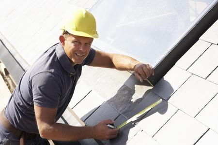 Dachdecker arbeiten an Außenseite des neues Zuhause Standard-Bild