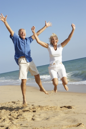 enjoy space: Senior Couple Enjoying Beach Holiday Jumping In Air