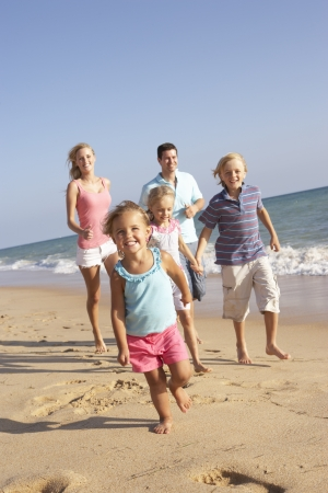 active family: Portrait Of Running Family On Beach Holiday Stock Photo
