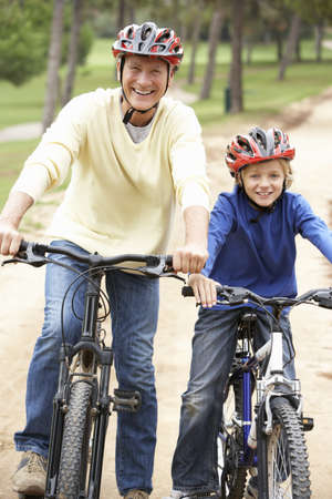 Grandfather and grandson riding bicycle in park Stock Photo - 9174794