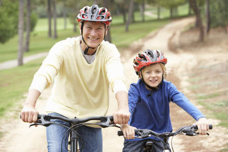 Grandfather and grandson riding bicycle in park Stock Photo - 9174779