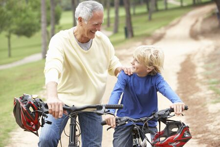 Grandfather and grandson riding bicycle in park photo