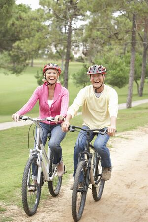 bike riding: Senior couple riding bicycle in park