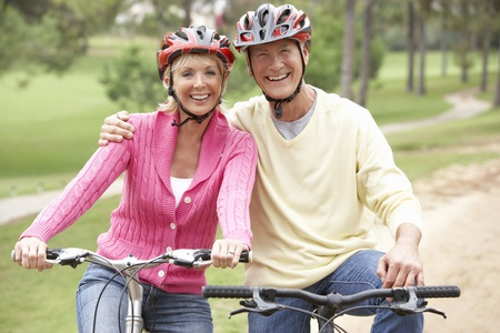 shoulder ride: Senior couple riding bicycle in park