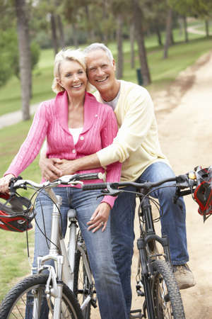 Senior couple riding bicycle in park photo