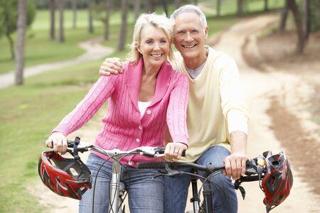 shoulder ride: Montar bicicleta de pareja Senior en Parque