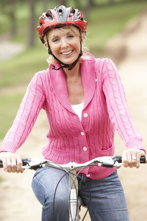 bike riding: Senior woman riding bicycle in park Stock Photo