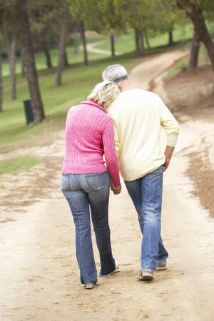 walking away: Senior Couple enjoying walk in park