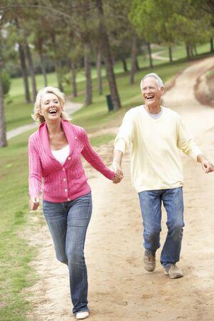 parejas caminando: Senior pareja disfrutando de paseo en el Parque Foto de archivo