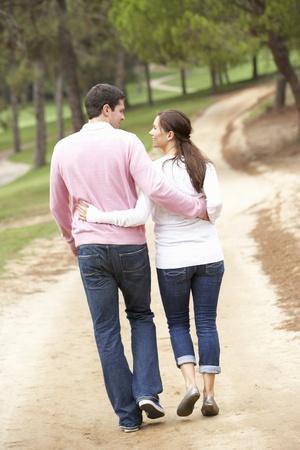 walking away: Romantic couple enjoying walk in park Stock Photo