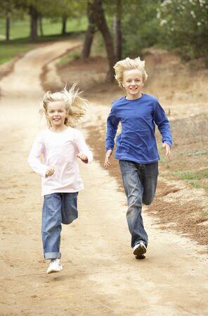 Two Children running in park photo