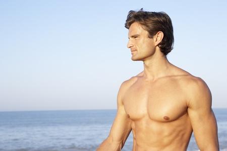 torso nudo: Giovane uomo pose sulla spiaggia