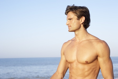 muscular man: Young man poses on beach