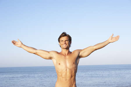 Young man stretching on beach photo