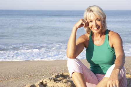 Senior woman sitting on beach relaxing Stock Photo - 9197364