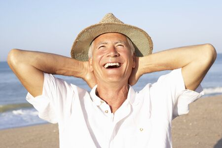 people laughing: Senior man sitting on beach relaxing