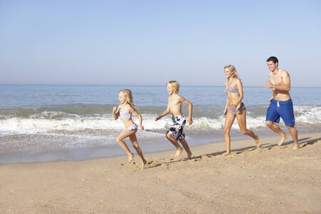 Young family running on beach photo