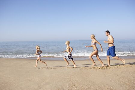 Young family running on beach Stock Photo - 9197388