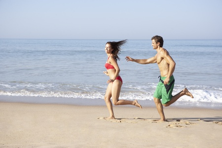 Young couple running on beach photo
