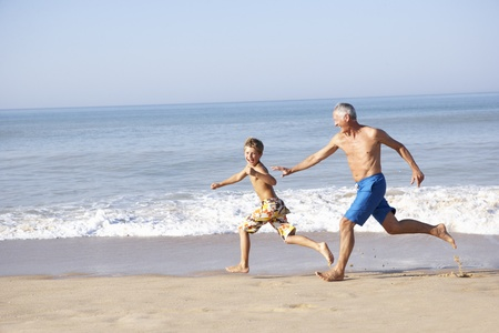 grandson: Grandfather chasing young boy on beach Stock Photo