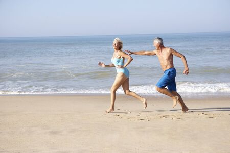 Senior couple running on beach photo