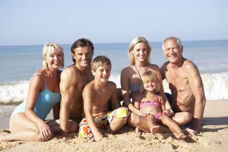 Three generation family pose on beach photo