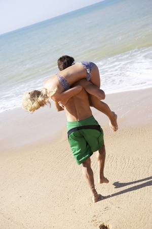 Young couple play on beach Stock Photo - 9197504