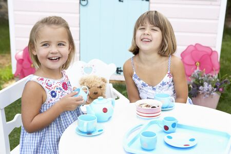 tea party: Two young girls play outdoors