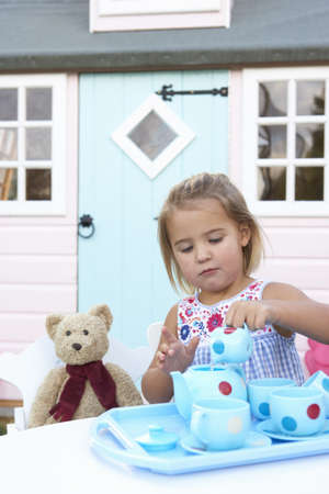 tea party: A young girl plays outdoors