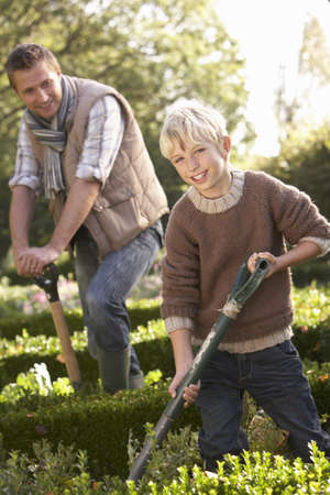 dug: Young man with child working in garden Stock Photo