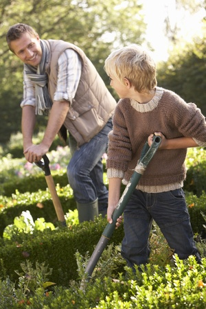 helping children: Young man with child working in garden Stock Photo
