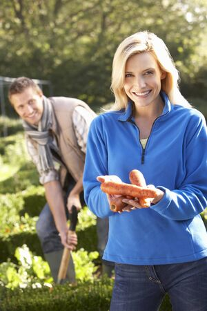 vegetables young couple: Young couple posing in garden Stock Photo