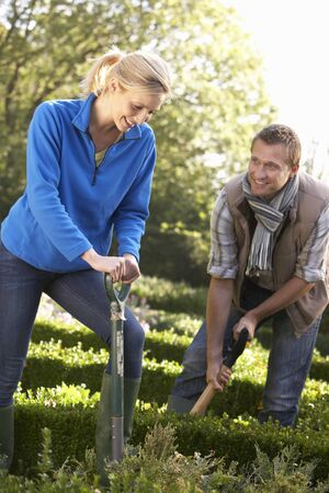 Young couple working in garden photo