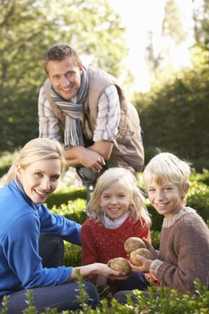 Young family sit together in garden photo