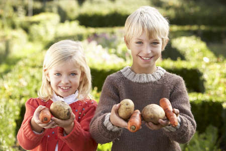 7 year old boys: Young children in garden pose with vegetables