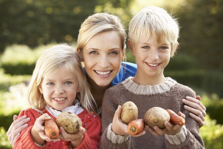 7 year old boys: Young mother and children in garden pose with vegetables Stock Photo