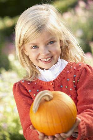 Young girl posing with pumpkin in garden photo